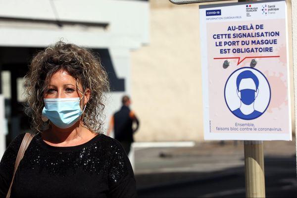 Une jeune femme avec un masque, à côté d'un panneau rappelant son port obligatoire - Photo d'illustration