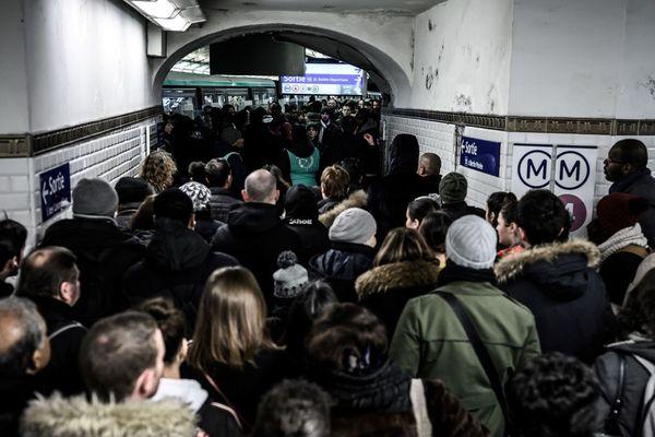 Des voyageurs font la queue en tentant d'emprunter la ligne 1 du métro parisien, lors de la grève du jeudi 12 décembre.