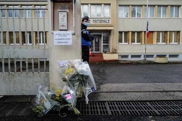 Un gendarme monte la garde près de bouquets de fleurs déposés devant l'entrée de la gendarmerie d'Ambert (Puy-de-Dôme) le 23 décembre 2020.