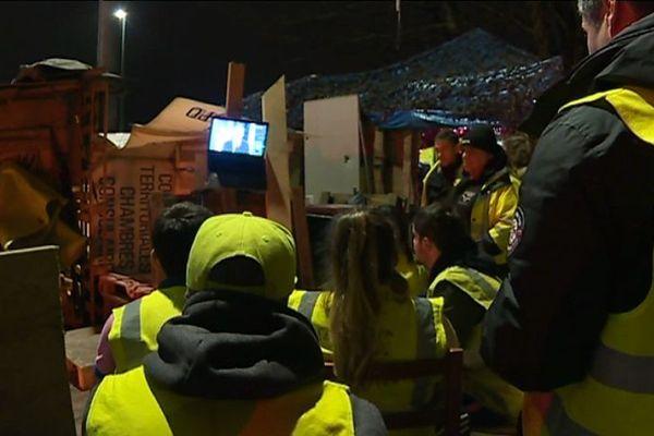 Des gilets jaunes écoutent le discours d'Emmanuel Macron, sur un rond-point, à Brest (29).
