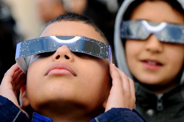 Deux enfants regardent une éclipse partielle de Soleil, le 4 janvier 2011, à Tunis (Tunisie).