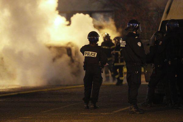 La police sécurise les pompiers qui interviennent sur une voiture en feu dans le quartier de Cronenbourg à Strasbourg le soir du réveillon.
