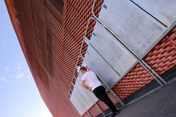 Un homme adossé à des panneaux électoraux vides de toute affiche - Photo d'illustration