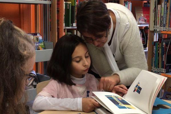 Petite fille lisant à la bibliothèque centre ville jeunesse de Dijon