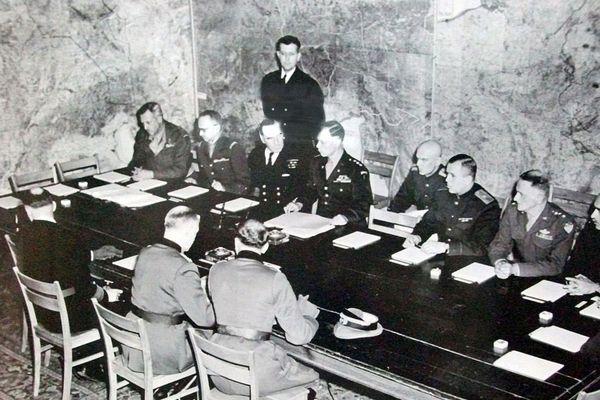 Signature de la reddition le 7 mai 1945 à Reims, par Major Wilhelm Oxenius, General Alfred Jodl, General Admiral Hans-Georg von Friedeburg (officiers allemands, tous trois de dos, de droite à gauche), sir F E Morgan, François Sevez, Harold Burrough, Harry C. Butcher, Walter Bedell Smith, K W D Strong, Ivan Cherniaev, Ivan Sousloparov, Carl Spaatz, Henri Bull (une très petite partie de sa tête est présente à l'angle de la table), John Robb, Ivan Zenkovitch (de face, de gauche à droite)