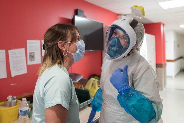 Une infirmière s'équipe du masque de chez Decathlon avant de rentrer dans la chambre d'un patient atteint par le Covid 19.
