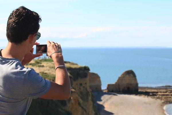 Un touriste prend en photo la Pointe du Hoc, située entre les plages de Utah Beach et Omaha Beach.
