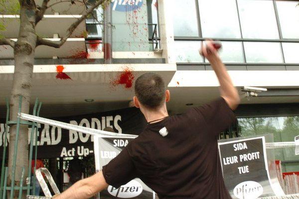 Un militant de l'association Act Up Paris lance des préservatifs de faux sang sur la façade du siège social du groupe pharmaceutique Pfizer France, le 26 avril 2005 à Montrouge.
