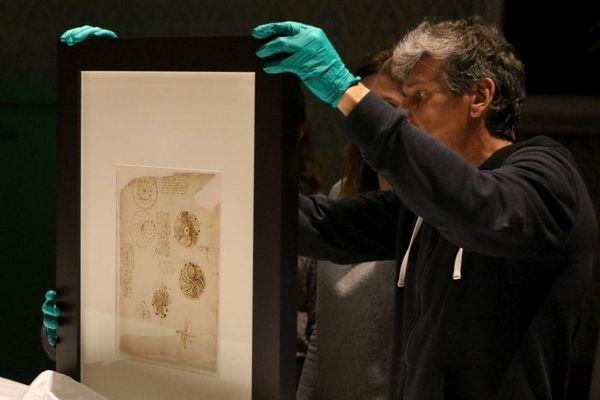 Codex Atlanticus de Léonard de Vinci : les conservateurs de Chambord examinant l'un des trois feuillets exposés du 25 mai au 1er septembre 2019 au château de François 1er..
