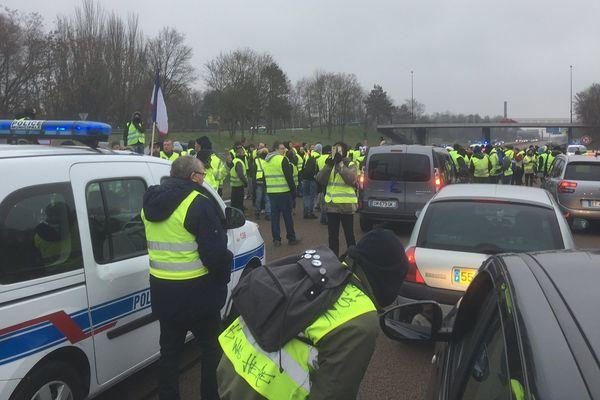 Sur la voie Taittinger à Reims, un gilet jaune explique les revendications du mouvement à un automobiliste.