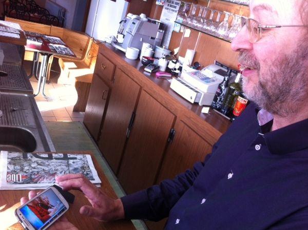 Michel Pennequin regarde sur son smartphone l'un des nombreux reportages télé fait sur la brasserie Chez Cathy