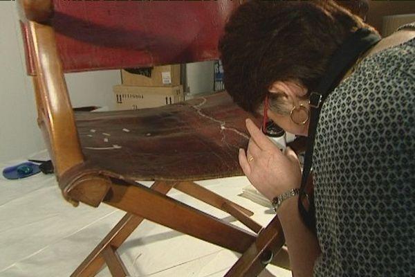 Le fauteuil de campagne de Napoléon fait l'objet d'un travail de restauration par une spécialiste du cuir.