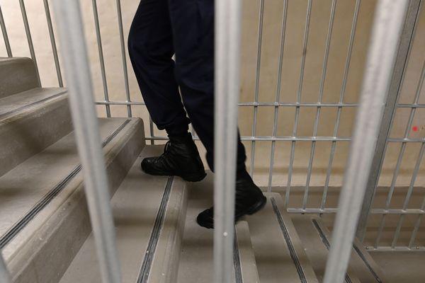 Un surveillant de prison monte un escalier derrière les barreaux - Photo d'illustration