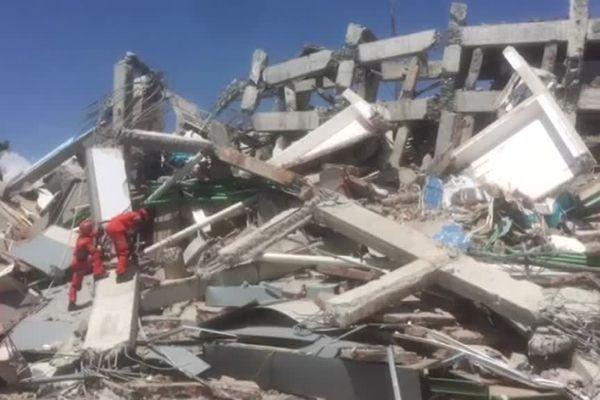 Les secours escaladent les décombres d'un immeuble détruit par le séisme sur l'île de Sulawesi, en Indonésie.