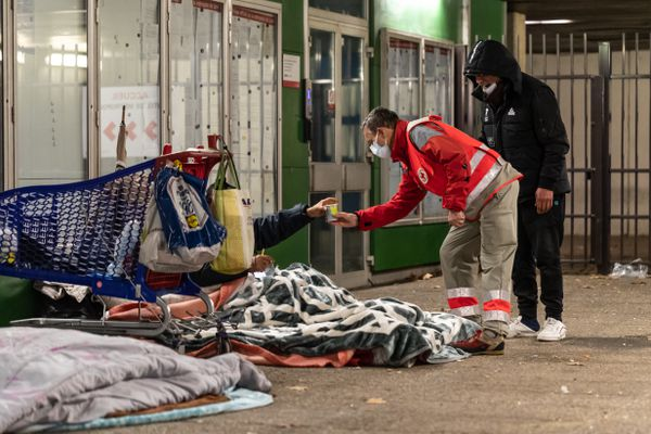 Illustration à Lyon , le 30 décembre 2020 . Un bénévole de la Croix-Rouge française donne un soupe chaude a une personne sans abris.
