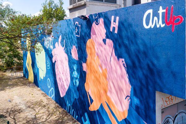 La fresque d'hommage aux soignants a été réalisée sur un mur d'un local technique du groupement est des Hospices Civils de Lyon. Bien visible depuis le périphérique, elle donne du baume au coeur des professionnels de santé qui luttent contre l'épidémie de Covid-19.
