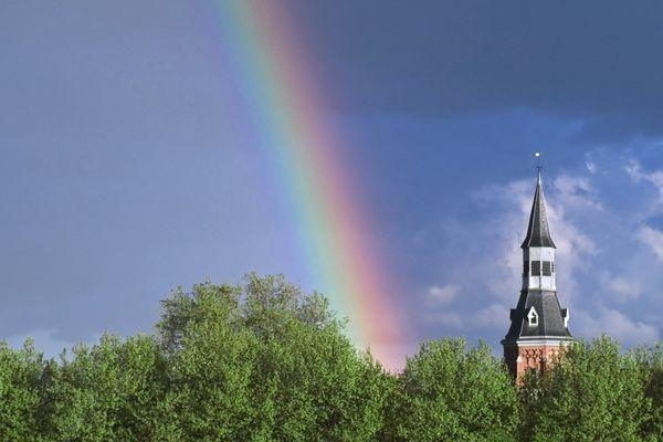 Rainbow and tower towering above trees | Arc-en-ciel et tour dominent les arbres