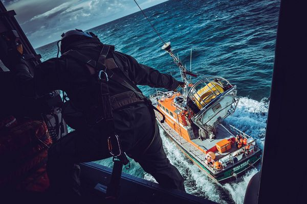 Un treuilliste hélicoptère réceptionne une civière de la SNSM à bord d'un Caïman Marine en exercice