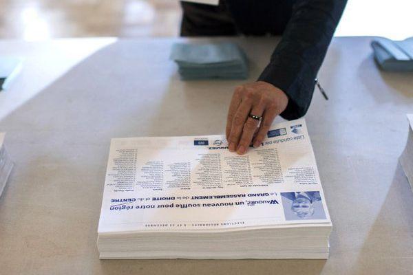 Une femme prend un bulletin de la liste de Laurent Wauquiez avant d'aller voter à l'occasion des élections régionales, le 6 décembre 2015 à Lyon.