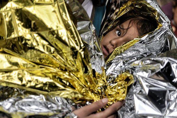 Un jeune Syrien est couvert par une couverture de survie à son arrivée sur l'île grecque de Lesbos, après avoir traversé la mer Égée depuis la Turquie, le 28 septembre 2015. Soixante-dix Syriens, dont cinq femmes et enfants se sont noyés en essayant de rejoindre la Grèce le 27 septembre 2015, après le nauffrage de leur bateau au large de la Turquie.
