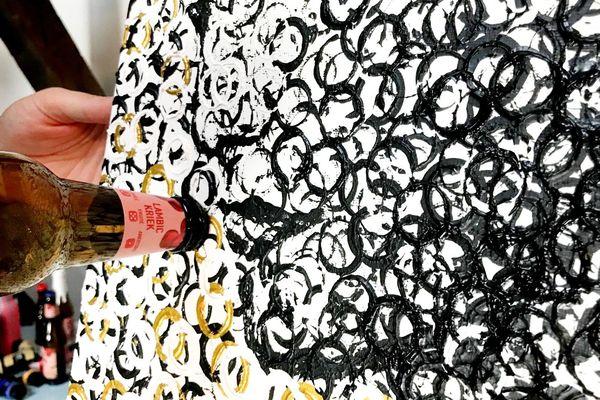 Le goulot de la bouteille de bière sert de pinceau dans le beerpainting