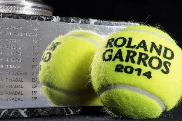 La célèbre Coupe des Mousquetaires avec le nom des différents vainqueurs de Roland Garros, et les balles de l'édition 2014 du tournoi.