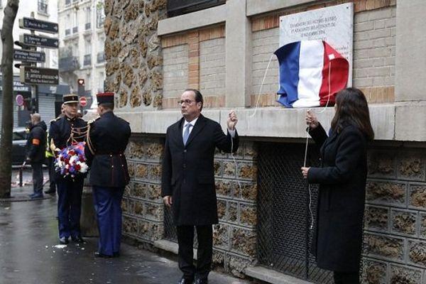 Le président français François Hollande et la maire de Paris Anne Hidalgo dévoilent une plaque commémorative à côté du bar et restaurant La Belle Équipe à Paris le 13 novembre 2016 lors d'une cérémonie marquant le premier anniversaire des attentats terroristes de Paris. 130 personnes ont été tuées le 13 novembre 2015.
