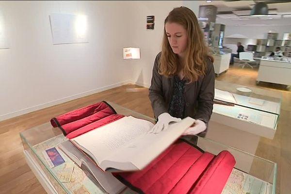 Héloïse Cuillier, directrice de la Bibliothèque Jacques Prévert à Cherbourg, manipule un des trois exemplaires de l'Encyclopédie de migrants présentés au public jusqu'au 29 décembre.