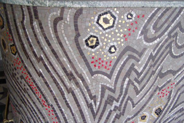 Le comptoir de béton armé est décoré de mosaïques mêlant deux teintes de gris en grès, le gris de pâtes de verre, le rouge et le noir d'opalines et l'or des émaux de Venise.