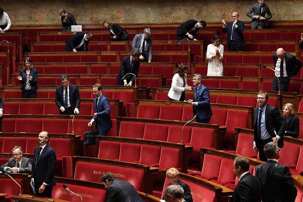 Le Premier ministre Edouard Philippe, se lève, mardi 28 avril, au moment des débats sur la présentation de son plan de déconfinement à l'Assemblée nationale. Seuls 75 députés ont pu siégé physiquement. Les autres ont participé et voté à distance.