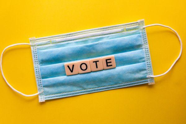 """Un masque avec déposé par dessus en lettre de scrabble le mot """"VOTE"""""""
