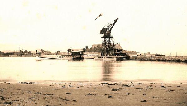 La grue Titan, qui remplace une première grue en bois,  permet, à partir du 30 novembre 1923, de mettre à l'eau les hydravions avec plus d'aisance. En arrière plan, le Fort Carré d'Antibes.