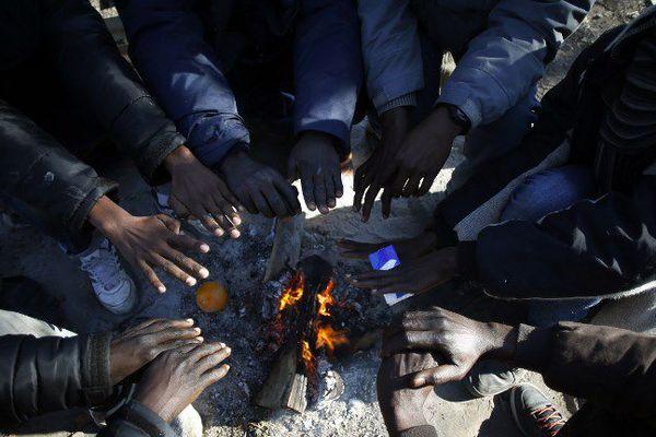 Des hommes se réchauffent les mains autour d'un feu, dans les bois près de Ouistreham (Calvados). Le 26 février 2018.