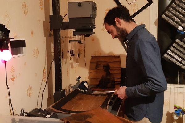 Julien Ermine dans son laboratoire, devant un tirage sur écorce