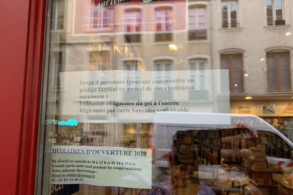 La porte d'entrée de la librairie s'est vêtue d'une nouvelle inscription : la jauge à quatre personnes maximum en même temps dans la boutique.