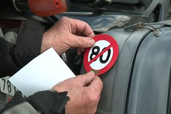 Un motard ajoute un autocollant sur son véhicule avant de prendre le départ de la manifestation ce samedi 14 avril.