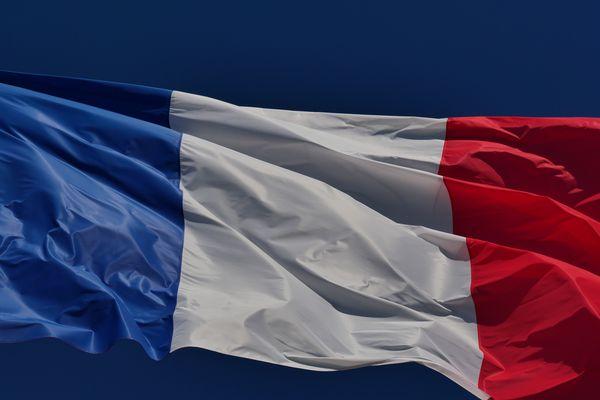Le drapeau français flottant dans les airs sous un ciel bleu.