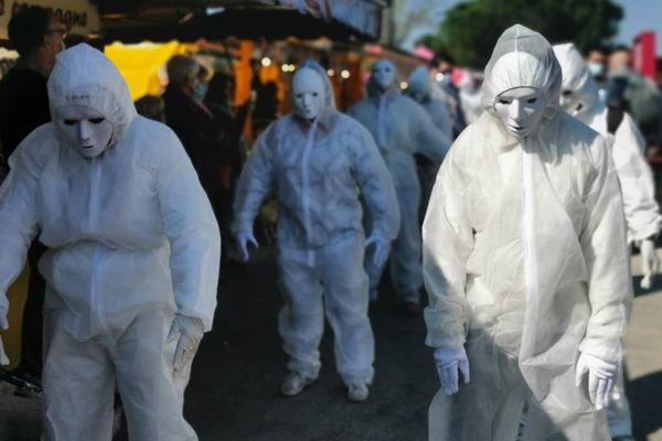 """Les """"masques blancs"""" ont défilé sur la place du marché de la Teste de Buch, sous les yeux ébahis des passants."""