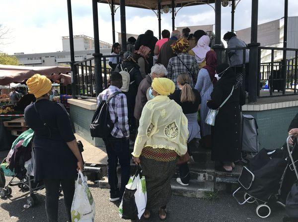Les familles dans le besoin font la queue devant le kiosque du marché pour bénéficier de ce que les commerçants donnent.