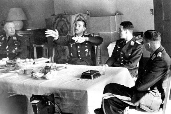 Adolf Galland mimant un combat aérien, en compagnie d'autres officiers de la Luftwaffe (Werner Mölders et Theo Osterkamp à droite), au Touquet, le 15 avril 1941.