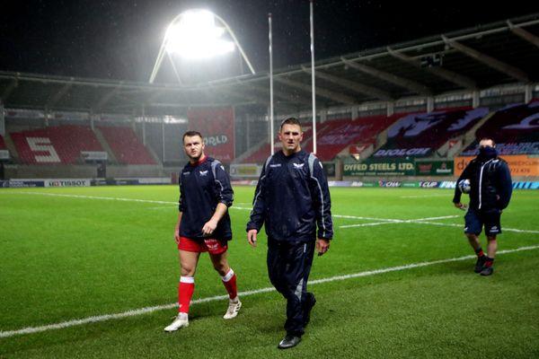 Deux joueurs des Scarlets quittent le terrain après le report de la rencontre vendredi dernier.