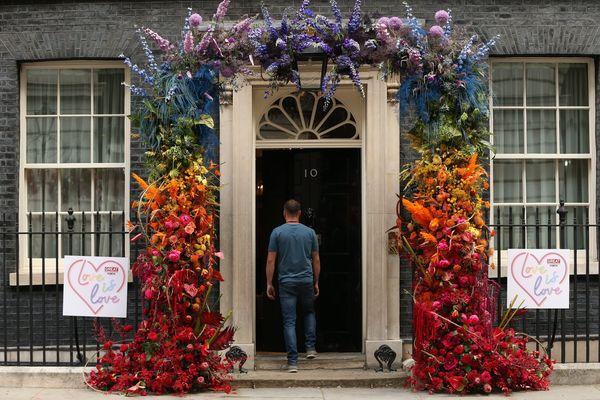 Un homme se présente à la porte du 10 Downing Street, décorée aux couleurs de la Pride - Photo d'illustration