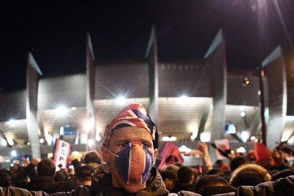Un supporter du PSG muni d'un masque aux couleurs parisiennes, devant le Parc des Princes, le soir de la qualification du club contre Dortmund (illustration).