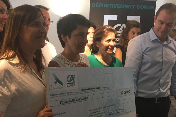 Le directeur général adjoint de la caisse régionale, Pascal Luigi, remet le chèque symbolique à la présidente Fabienne Giovannini (au centre) et à la directrice de l'OPH2C, Annie Albertini (à gauche)