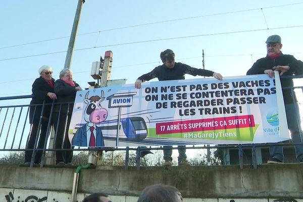 Les manifestants déployant une banderole pour dénoncer la suppression d'arrêts de trains en gare d'Avion.