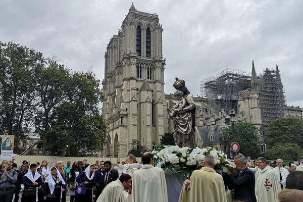 La tête du cortège et Notre-Dame en arrière-plan, quatre mois après l'incendie.