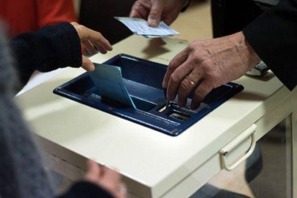 Un électeur dépose un bulletin dans l'urne à Forcalquier.