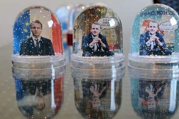 """L'entreprise Bruot, dans l'Ain, fabrique des boules à neige à l'effigie d'Emmanuel Macron : sur fond tricolore arborant les étoiles européennes, """"Et en même temps"""", """"Vivement le Touquet""""."""