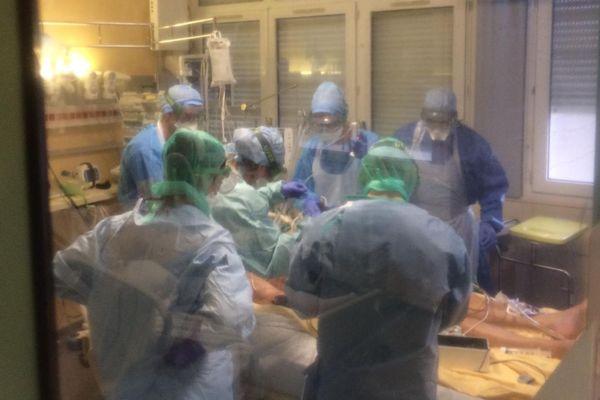 L'un des deux malades arrivés en début de soirée à l'hôpital Clermont Tonnerre de Brest, entouré de nombreux soignants. Pour des raisons de protection face à la contamination, notre matériel de tournage était emballé dans du film plastique transparent.