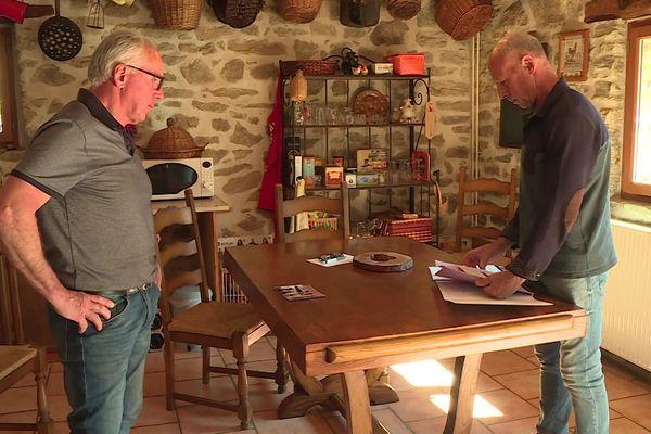 Didier et Denis Bordes choisissent une photo de leur père pour mettre sur la tombe